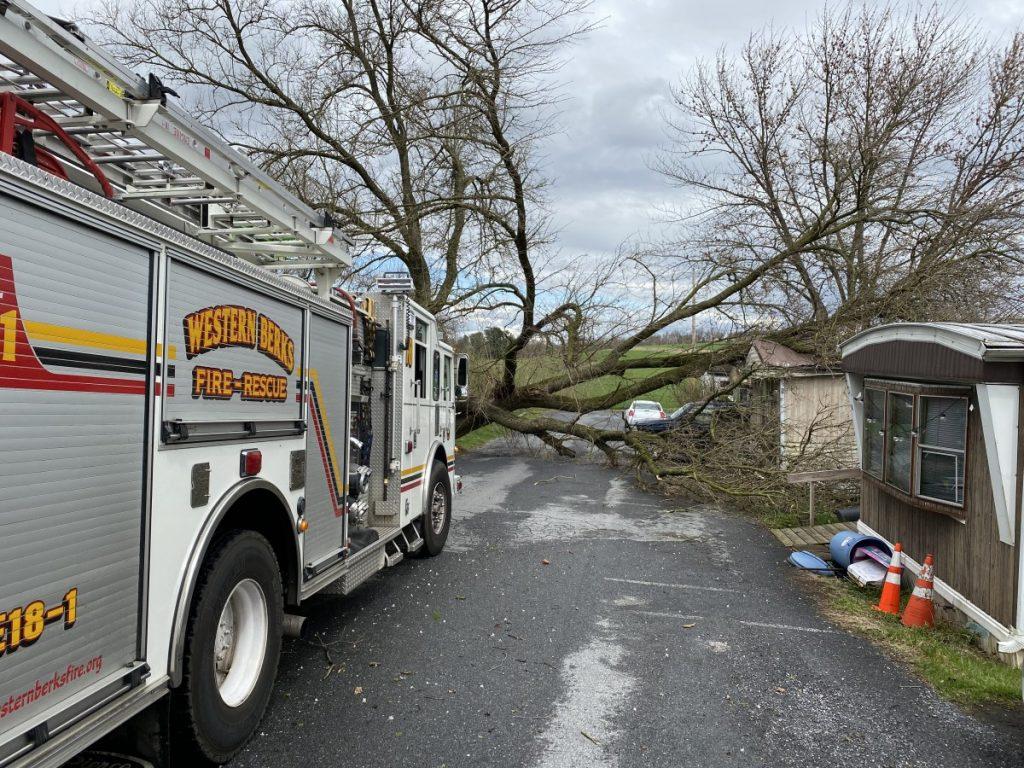 Engine 18-1 on scene with a tree onto a house
